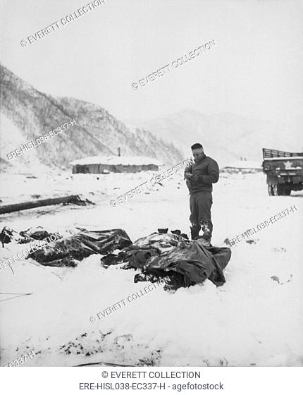 A wounded chaplain reads a memorial service over the snow-covered bodies of dead Marines. At Kotori, Korea, south of the Chosin reservoir where U.S