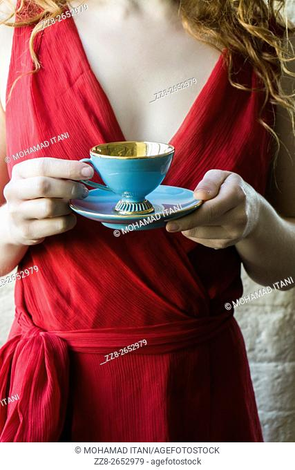 Close up of a woman in red holding a vintage teacup and saucer
