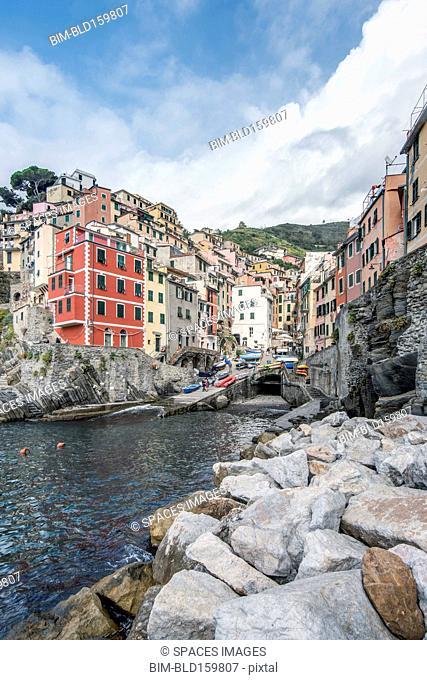 Buildings and rocky coastline near harbor, Manarola, La Spezia, Italy
