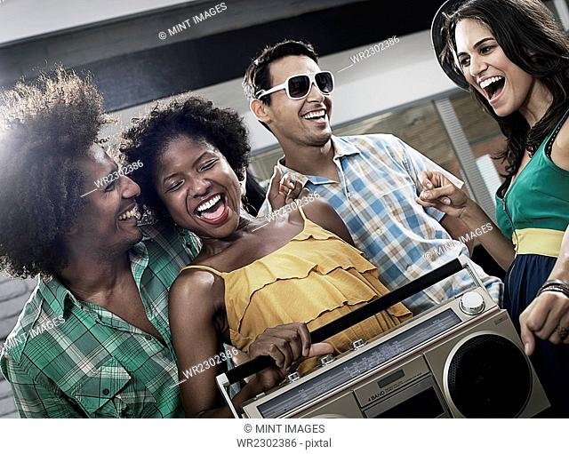 Four friends with a large portable music player, having a party