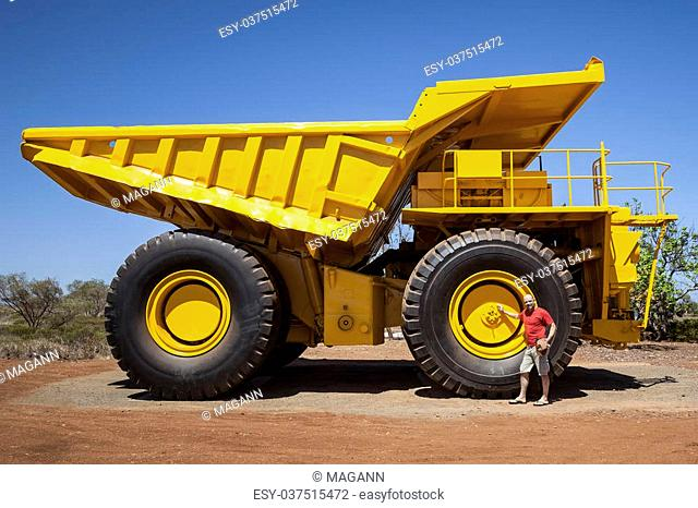 An image of a big yellow transporter and a man in front of a wheel
