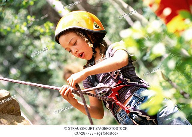 Young girl learning to tie knot before climbing rock face at rock climbing school