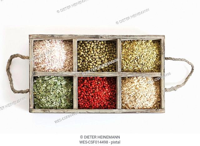 Variety of spices and herbs in wooden box on white background