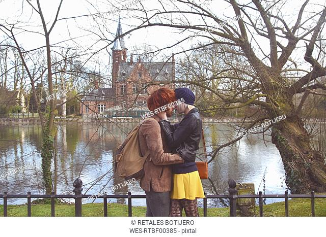 Belgium, Bruges, young couple kissing at Minnewater