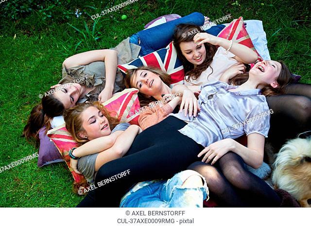 Teenage girls laying on pillows outdoors
