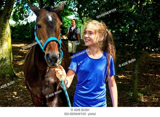 Girl holding lead rope looking at horse smiling