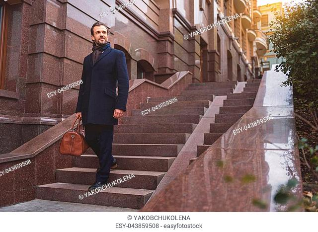 Happy man is going downs stairs and carrying baggage for business trip. He is looking forward with aspiration and smiling