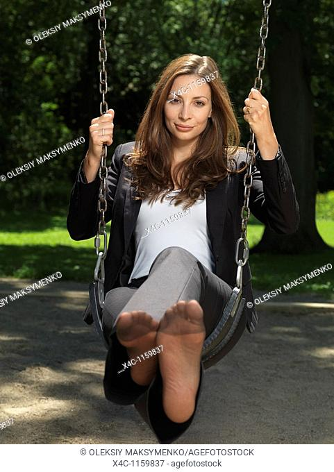 Young attractive businesswoman sitting barefooted on a swing in a park