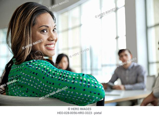 Beautiful businesswoman looking away with colleagues in background