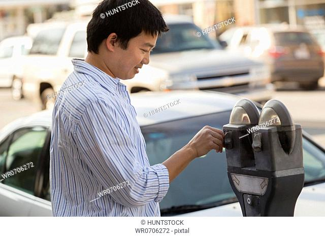 Chinese man putting money in a parking meter