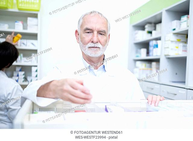 Pharmacist taking medicine from cabinet in pharmacy