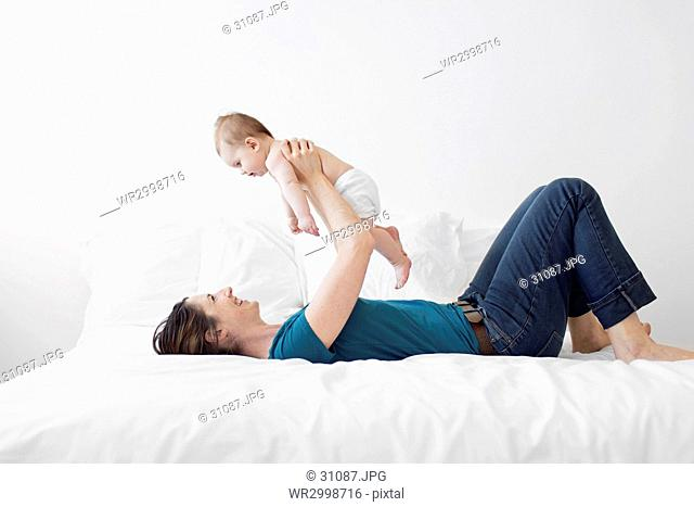 Woman wearing blue top and jeans lying on a bed, holding aloft baby girl
