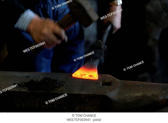 Germany, Bavaria, Josefsthal, blacksmith beating glowing axe on anvil with hammer