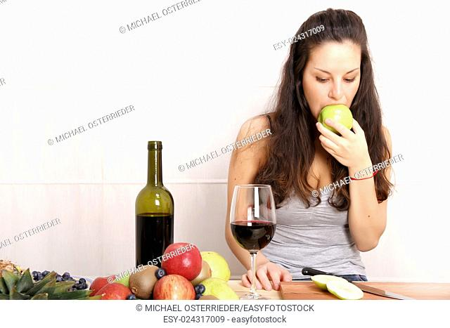 A young adult woman with fruits and wine in the kitchen