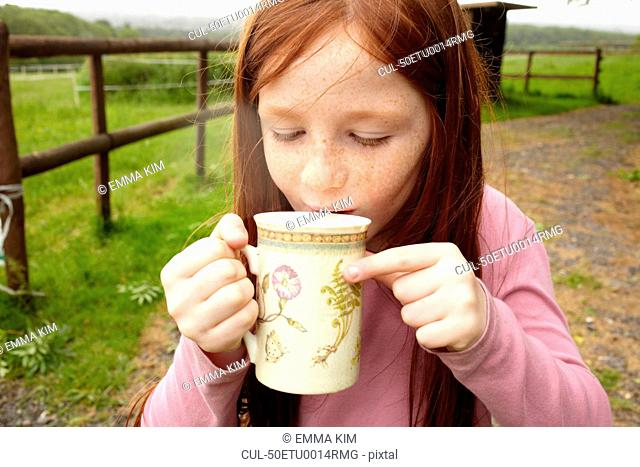 Girl drinking cocoa outdoors