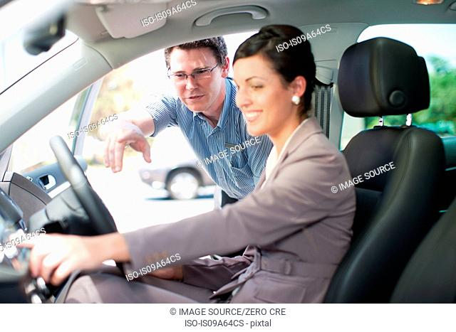 Salesman showing woman new car