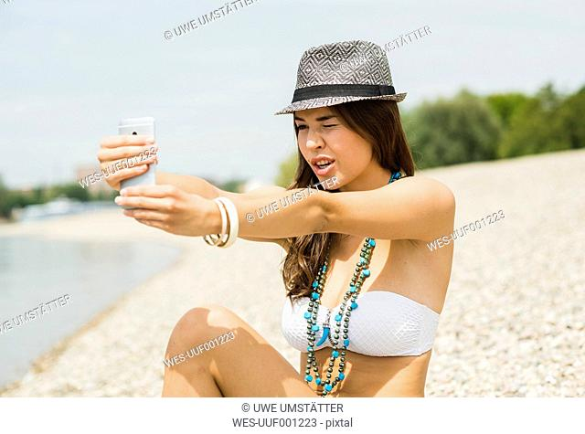 Portrait of young woman taking a selfie with her smartphone on the beach