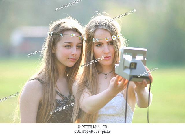 Two teenage girls in park taking instant camera selfie