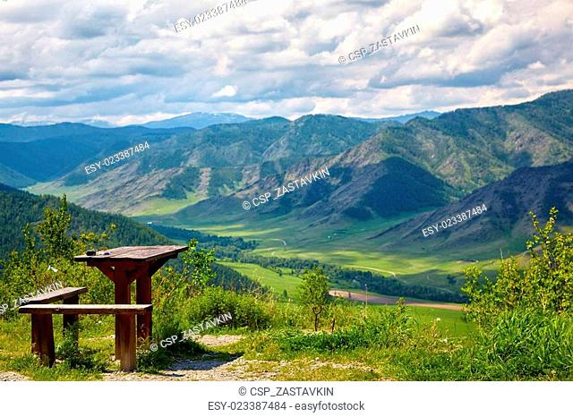 Wooden table and bench on the top of mountain pass Chike-Taman in Russia