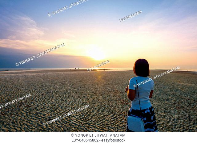 Women tourist standing on the beach watching the beautiful natural landscape, colorful of the sky and the sea during a sunset at Nathon Sunset Viewpoint in Ko...