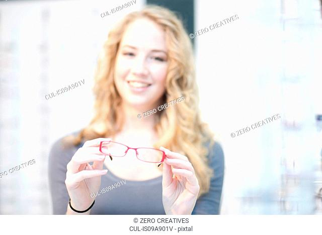 Young woman holding eyeglasses