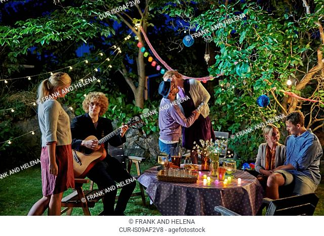 Three couples enjoying evening garden party