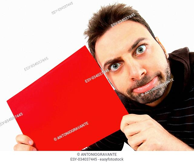 Young man with funny expression while keeps red billboard
