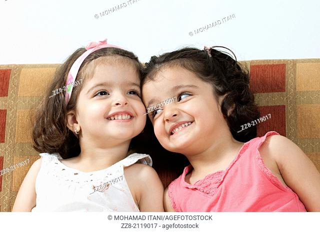 3 years old twin sisters smiling