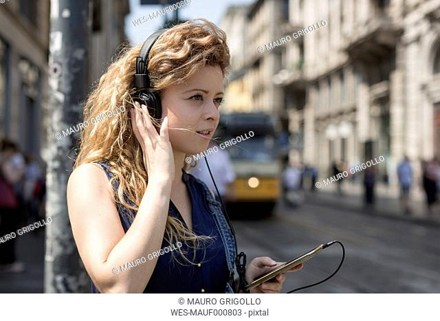 Italy, Milan, portrait of young woman with headphones and smartphone