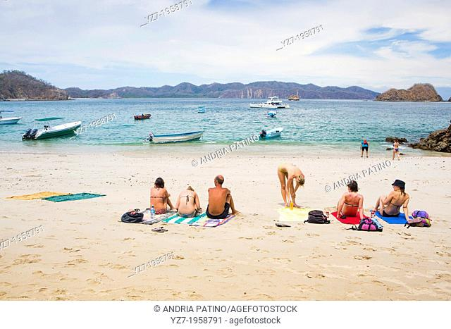 Visitors enjoying the sun at Isla Tortuga beach, Costa Rica