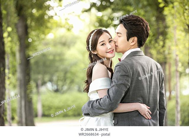 Back portrait of young wedding couple kissing outdoors