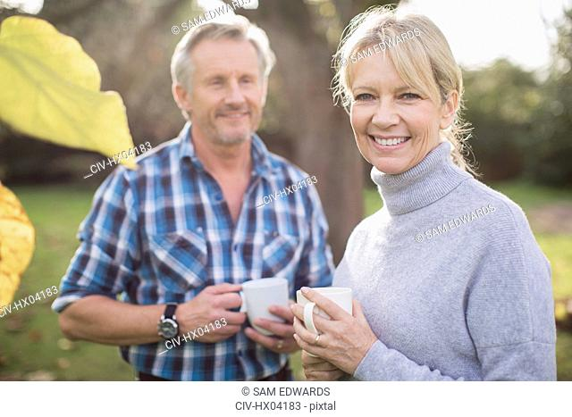 Portrait smiling, happy mature couple drinking coffee in backyard