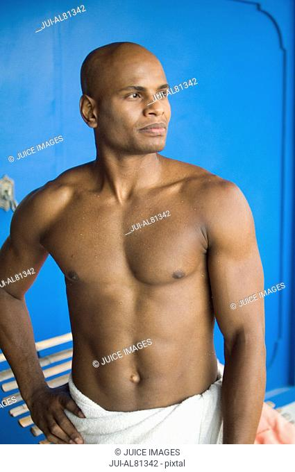 African man wearing towel with hand on hip