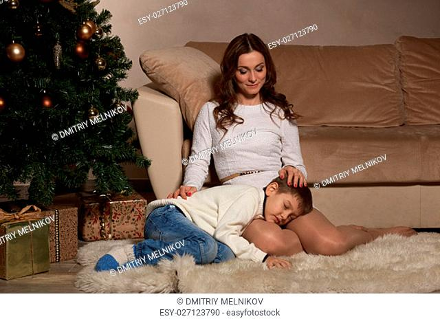 Happy family are sitting on a floor near Christmas tree at home. Merry Christmas and Happy New Year. Beautiful young mother with son