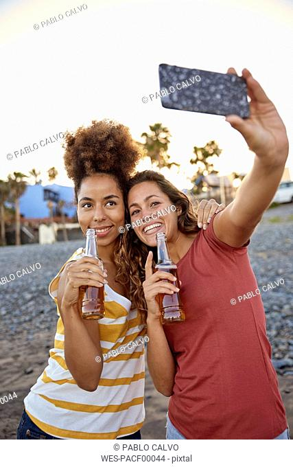 Two best friends taking selfie on the beach