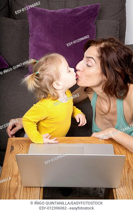 nineteen month aged blonde baby yellow shirt with pigtails and brunette woman mother kissing in mouth with grey laptop on brown table