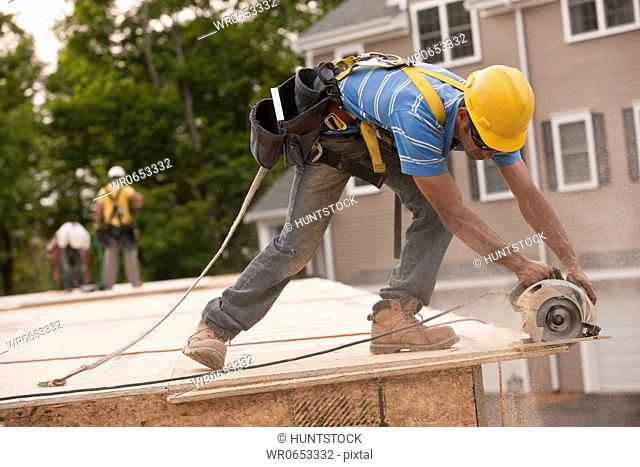 Carpenter sawing a particle board