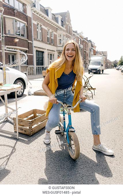Belgium, Tongeren, happy young woman on a children's bicycle on an antique flea market