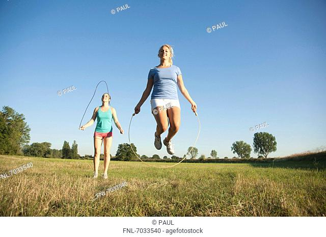 Two young women skipping rope on meadow