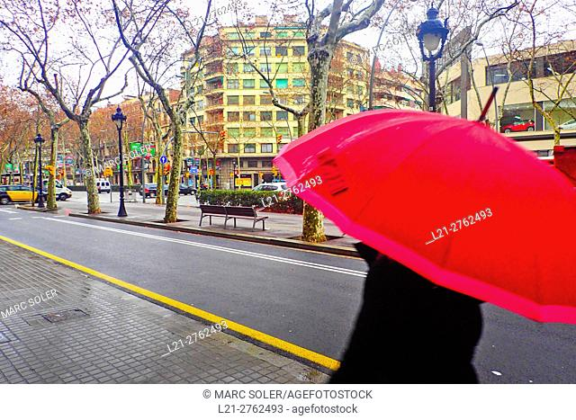 Someone with red umbrella walking along a street in a rainy day. Barcelona, Catalonia, Spain