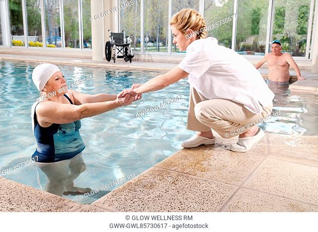 Health worker assisting a woman pulling out from a swimming pool