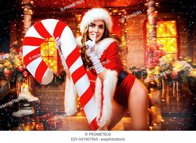 Sexy Santa girl in red body suit and striped stockings holds a big lollipop and poses near the house of Santa, decorated with festive lights
