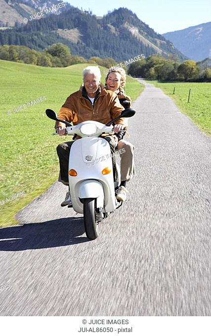 Senior couple riding motor scooter in rural area