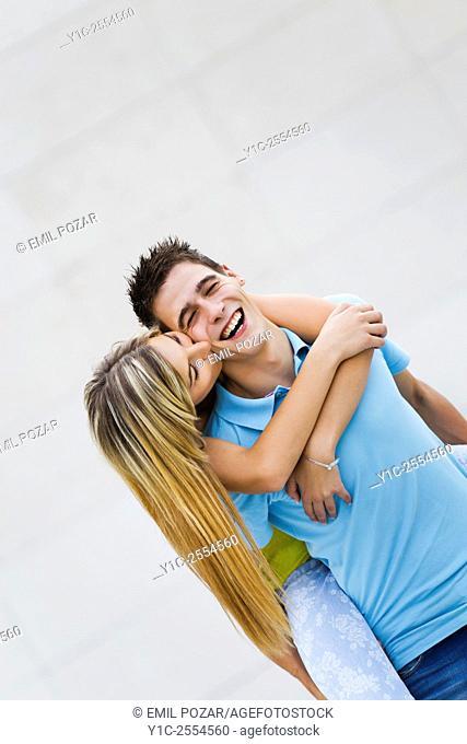 Teen couple girl and boy passionate hug and kiss