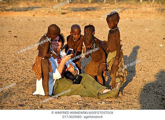 Tourist and Himba children. Kaokoveld, Northern Namibia