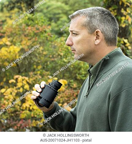 Side profile of a mature man holding binoculars