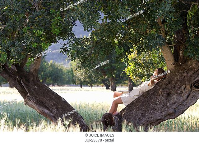 Woman laying against tree with laptop