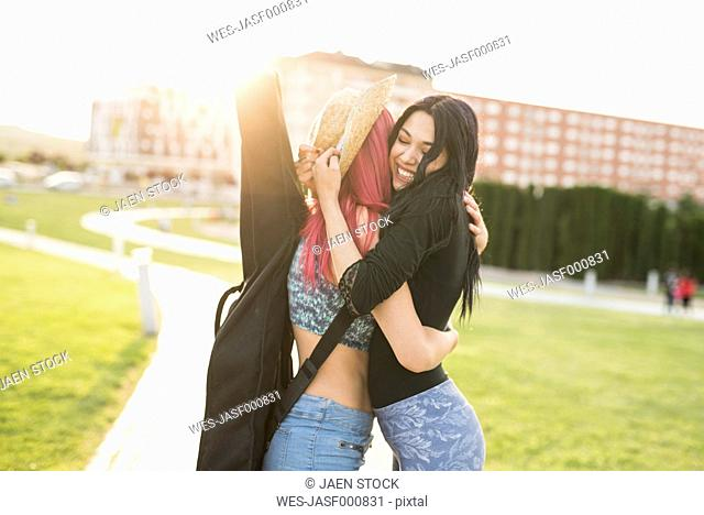 Two young women hugging in park