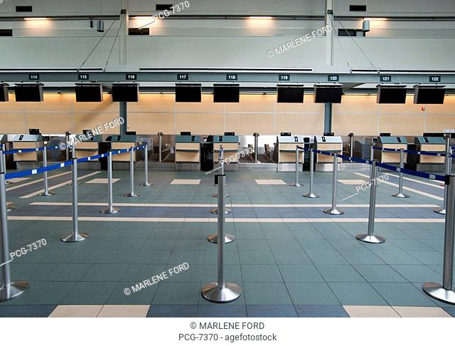 Rows of closed check in desks at Vancouver Airport. Blank information screens, metal posts for control of queues in place in rows. Empty space