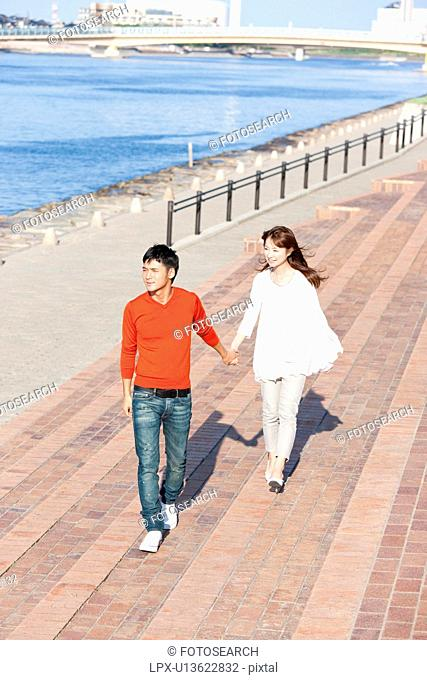 Young couple walking by the river, Hyogo Prefecture, Honshu, Japan